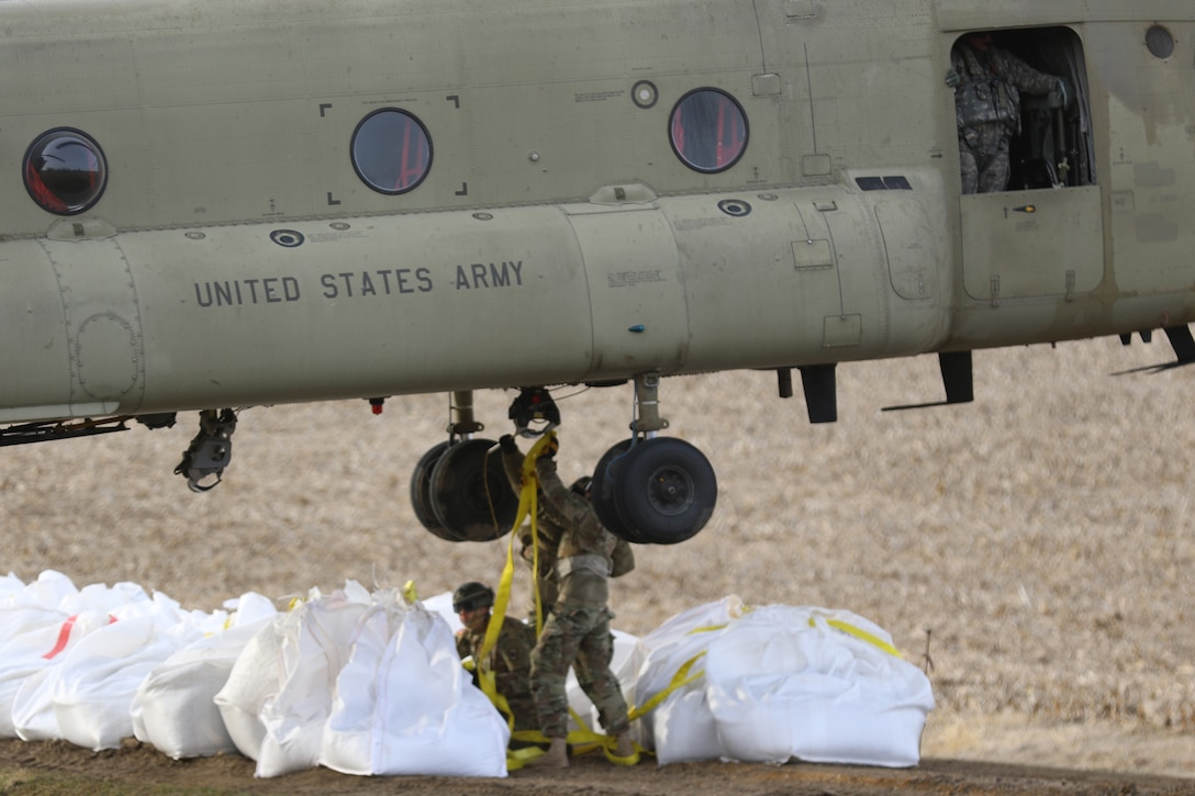 National Guard members attach sandbags to be carried by a helicopter in slings.