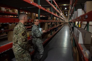 U.S. Air Force Tech Sgt. Nicole Finnegan, 97th Logistics Readiness Squadron NCO in charge of storage and issue, showcases the supply facility to Chief Master Sgt. Erik Thompson, command chief of the 19th Air Force