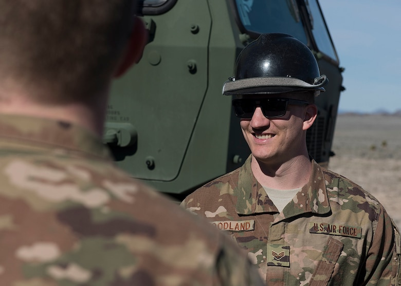 An Airman wears a hardhat while smiling.