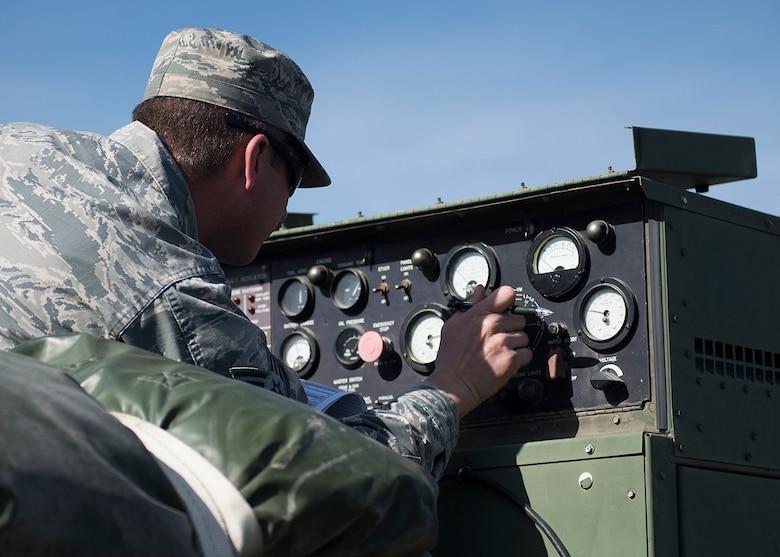 An Airman adjusts dials on a panel.