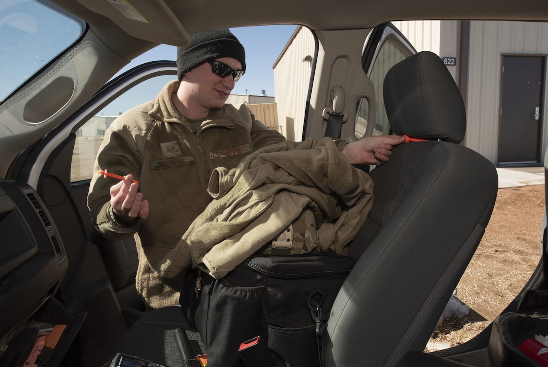 """Staff Sgt. Jeremiah Williams, 50th Security Forces Squadron investigator, discovers contraband during a vehicle search training scenario at the 50th SFS training facility at Schriever Air Force Base, Colorado, March 16, 2019. The training flight uses a """"crawl, walk, run"""" method for training sessions, a philosophical and practical approach to training used not only in the field, but classrooms as well.  (U.S. Air Force photo by Staff Sgt. Matthew Coleman-Foster)"""