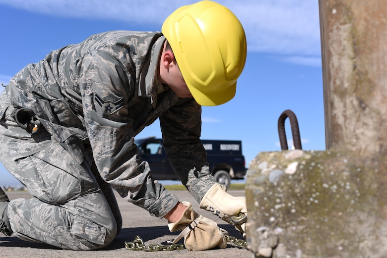 An Airman assigned to the 39th Maintenance Squadron ties a chain around a jersey barrier for support prior to lifting an F-4 Phantom II during an exercise March 8, 2019, at Incirlik Air Base, Turkey.
