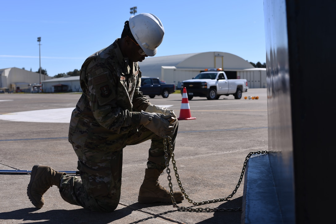 Airman 1st Class Jamere Morris, 39thMaintenance Squadron crew chief, ties a chain to a jersey barrier to stabilize cables attached to an F-4 Phantom II March 8, 2019, at Incirlik Air Base, Turkey.