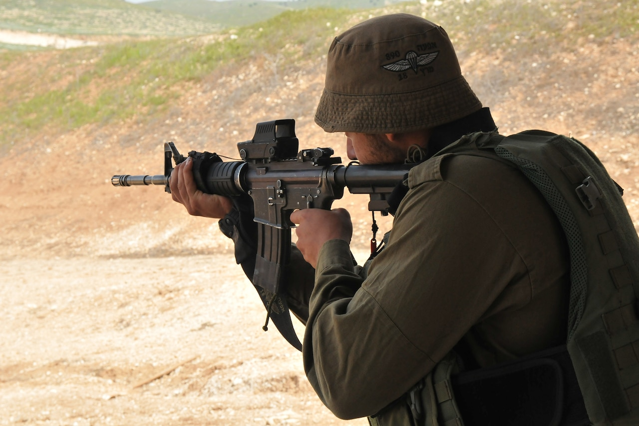An Israeli soldier fires a rifle.