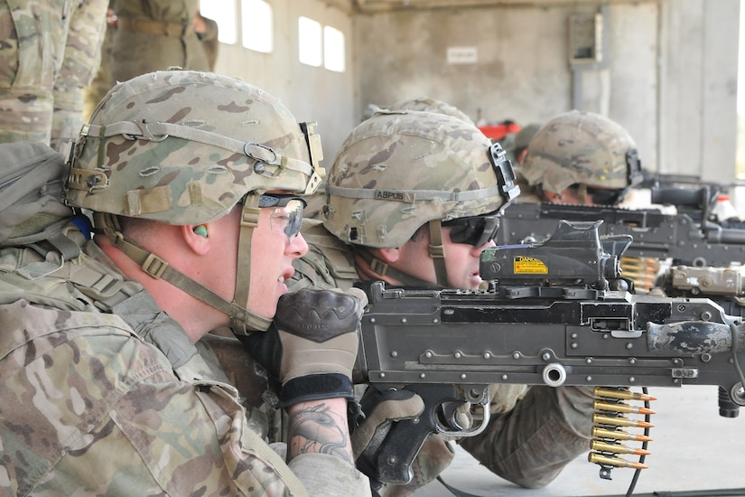 Soldiers fire machine guns.