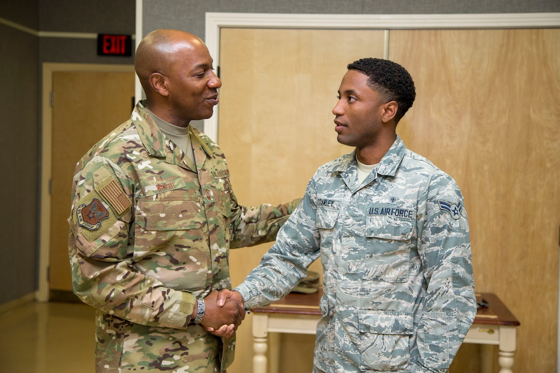 Chief Master Sgt. of the Air Force Kaleth O. Wright (left) presents a challenge coin for a job well done to Airman 1st Class Thierry Crawley, 412th Medical Group, Mental Health technician, March 19, 2019. (U.S. Air Force photo by Christopher Okula)