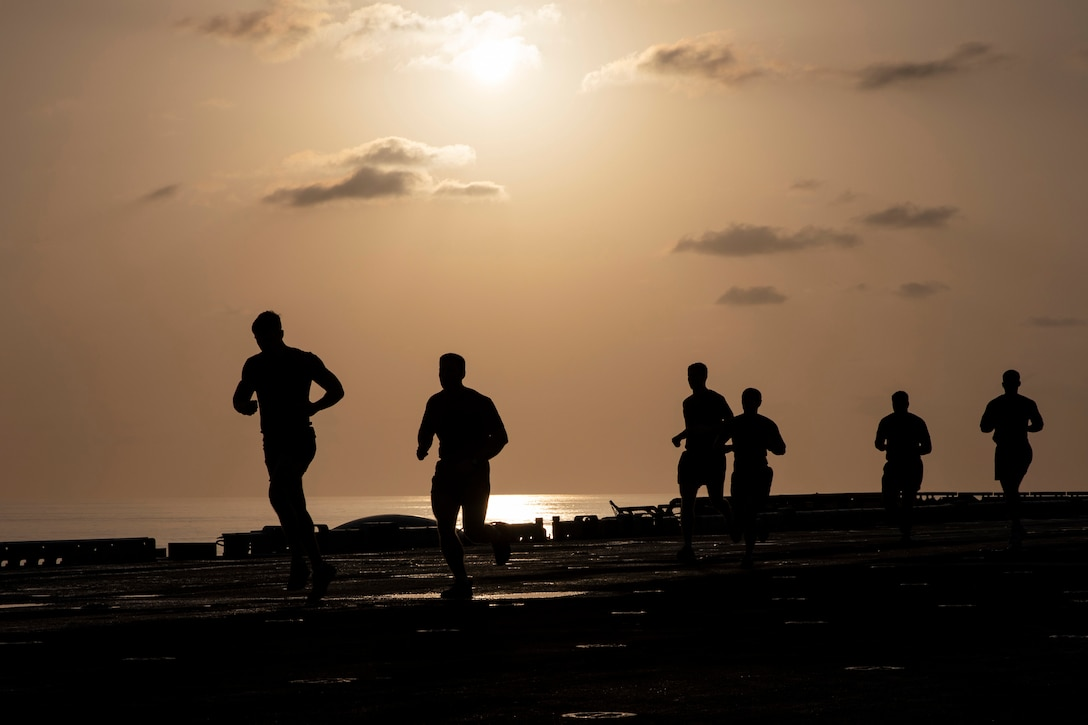 Six men are silhouetted against the sky as they run along the flight deck of a military ship.