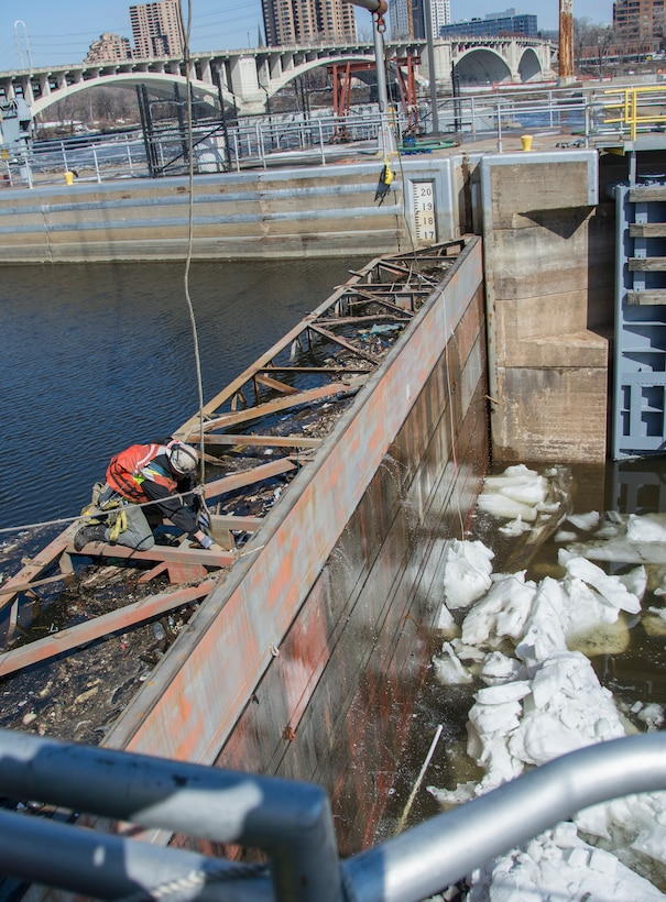 man attaches crane rope to bulkhead on river for removal