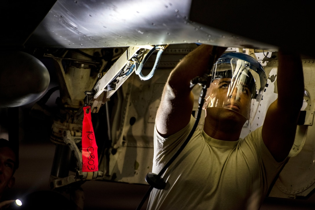 An airman works on the landing gear of an airplane.