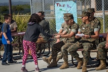 "U.S. Marines with Bridge Company, 7th Engineer Support Battalion, 1st Marine Logistics Group, and contractors with Facilities Maintenance Department, Marine Corps Installations West, Marine Corps Base Camp Pendleton, receive ""thank you"" letters from students at Santa Margarita Elementary School on MCB Camp Pendleton, California, March 18, 2019. The students of the elementary school wrote personal ""thank you"" letters to the Marines and contractors for building a bridge over and repairing a sinkhole in Carnes Road that resulted in the evacuation and temporary closing of the school on Feb. 4. The sinkhole was caused by erosion resulting from persistent heavy rain storms that swept through Southern California."