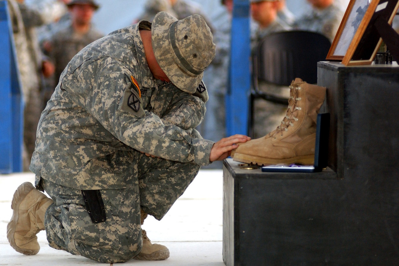 A soldier kneels with head down in front of a memorial that includes a boot and photo frames.