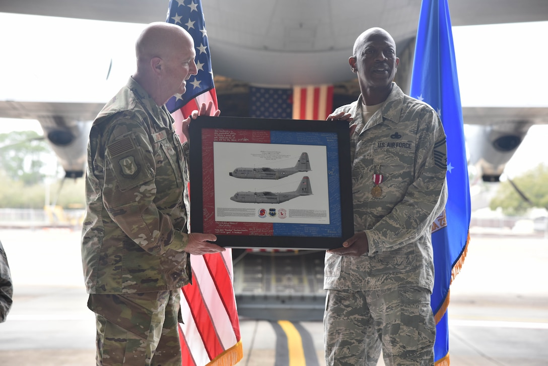Senior Master Sgt. Charles Moore, 803rd Aircraft Maintenance Squadron production superintendent, accepts framed C-130J Super Hercules aircraft artwork from Col. Jay Johnson, 403rd Maintenance Group commander, during Moore's retirement ceremony, March 8, 2019.  Moore officially retires April 1, 2019, after serving 33 years in the Air Force Reserve. (U.S. Air Force photo by Tech. Sgt. Michael Farrar)