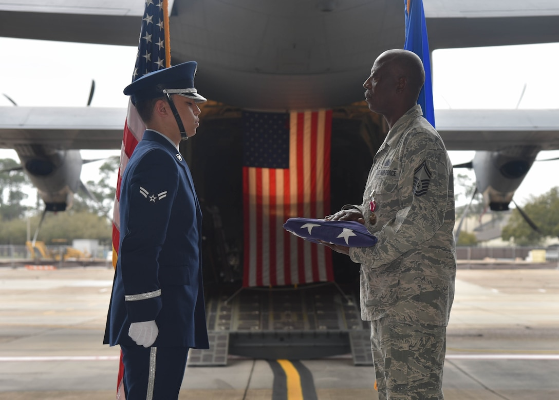 Senior Master Sgt. Charles Moore, 803rd Aircraft Maintenance Squadron production superintendent, accepts folded U.S. flag from an Honor Guard Airman during Moore's retirement ceremony, March 8, 2019.  Moore offiicially retires from his duties after serving 33-years in the Air Force Reserve, April 1, 2019. (U.S. Air Force photo by Tech. Sgt. Michael Farrar)