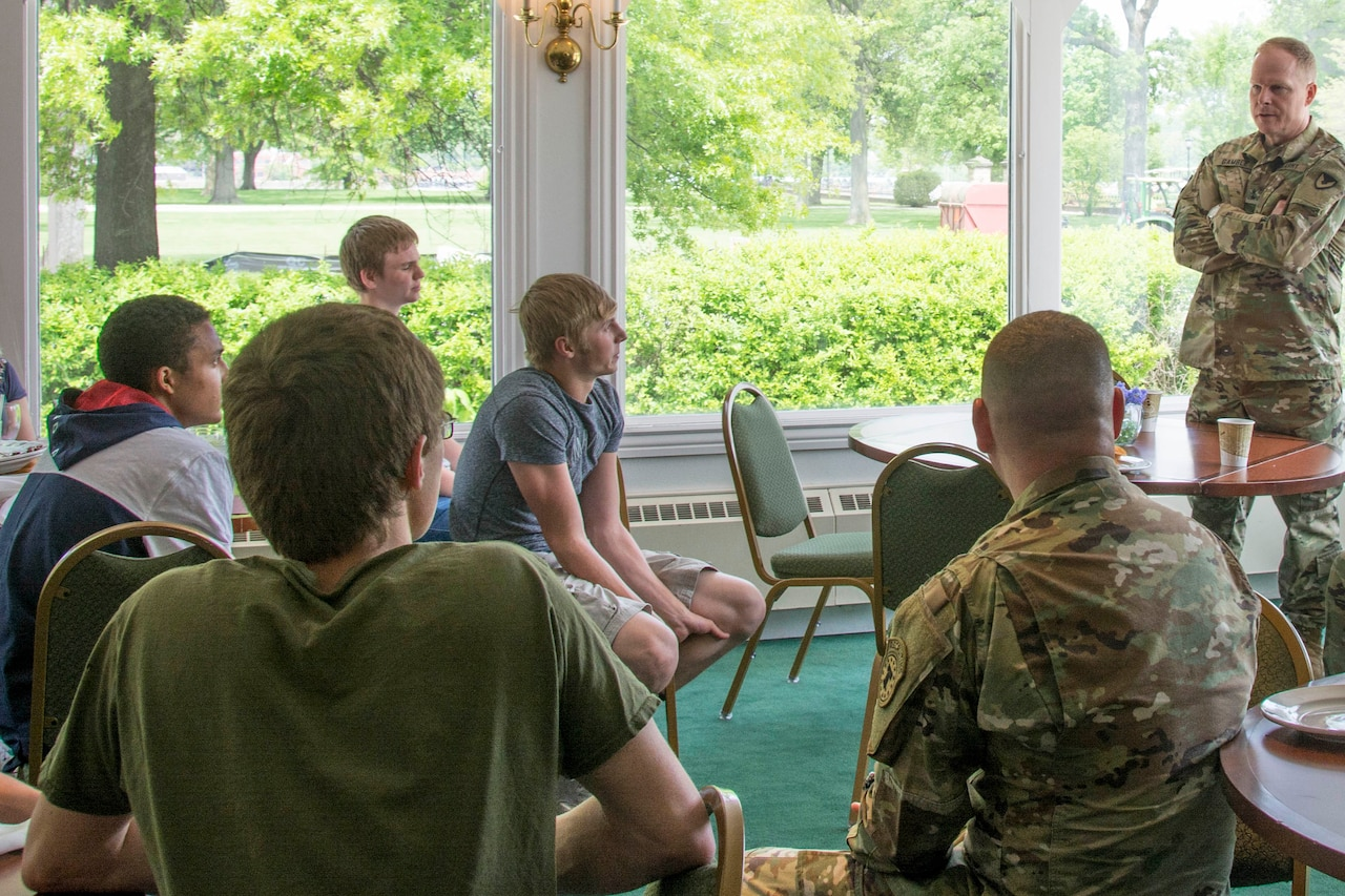 A soldier in a camouflage uniform speaks to a group of high school students.