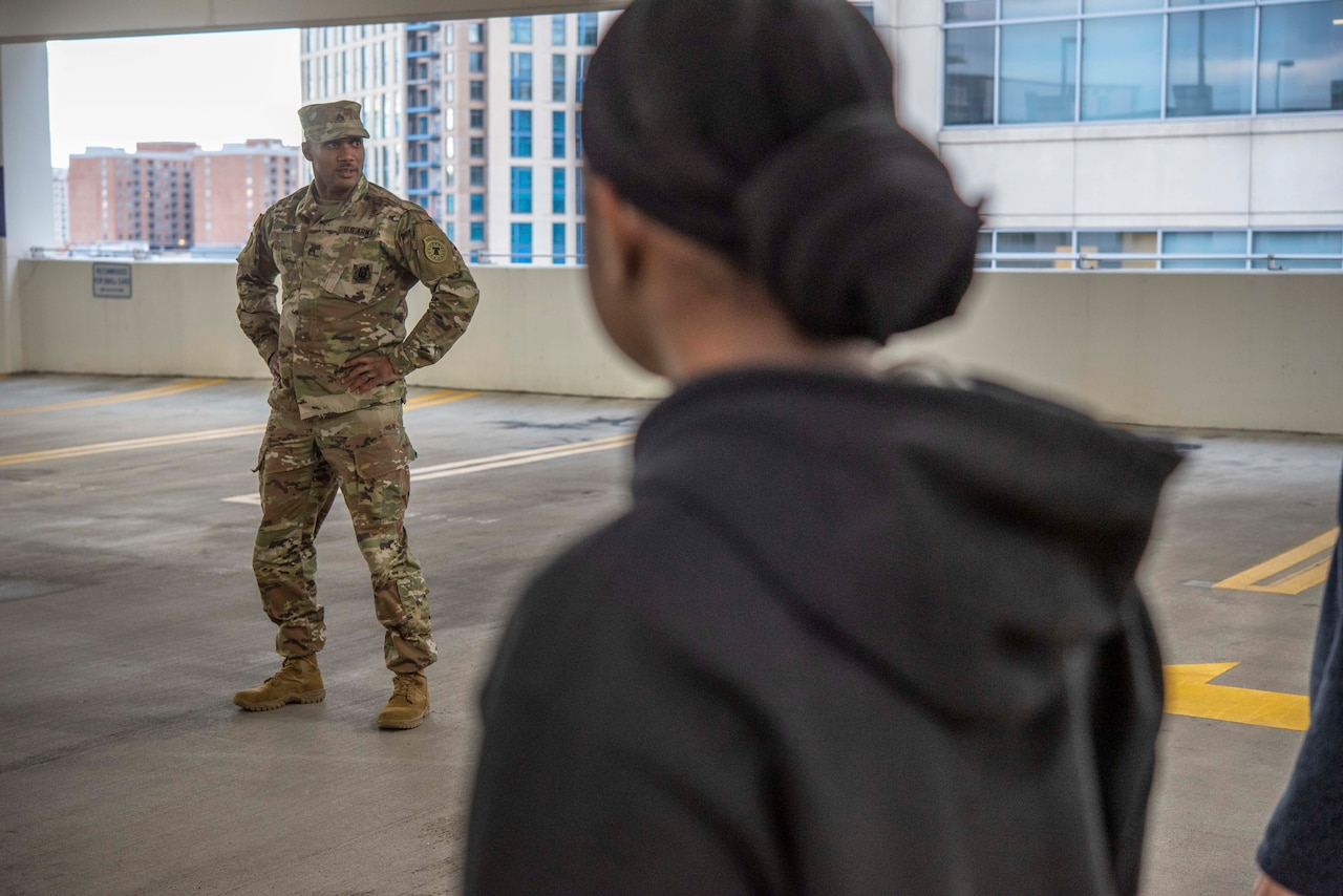 A soldier in camouflage stands with his arms akimbo in a parking garage.