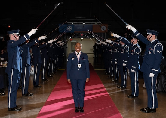 Senior Airman Mutia Graham, Air Force Test Center, walks through a formation of sabers during Air Force Materiel Command's Annual Excellence Awards Banquet March 6, 2019, at Wright-Patterson Air Force Base, Ohio. (U.S. Air Force photo by Michelle Gigante)
