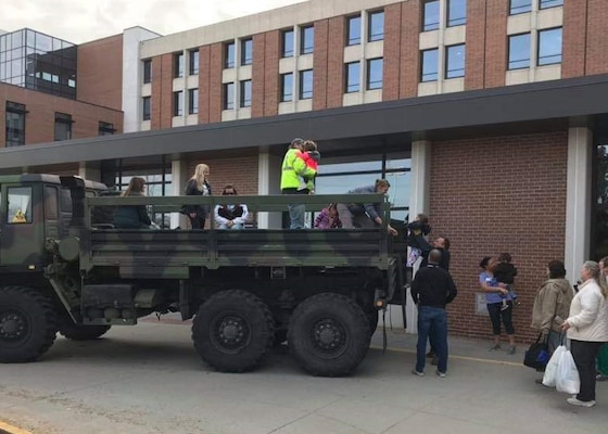 Stranded hospital staff and family members are loaded into a former military truck to be transported home, away from flood waters in Fremont, Nebraska.  After the emergency is over the truck will be converted for use in firefighting and then issued to a volunteer fire department.