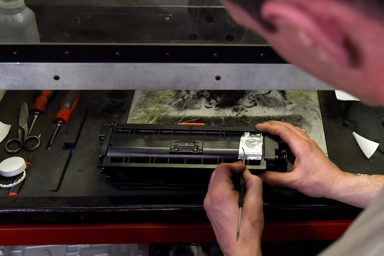 U.S. Air Force Staff Sgt. Tyler Ferris,  92nd Maintenance Group Air Force Repair Enhancement Program technician, prepares to refill an ink cartridge at Fairchild Air Force Base, Washington, March 20, 2019.The AFREP team has implemented environmentally friendly practices through recharging ink cartridges to mitigate the many adverse effects of just throwing them away. Like electronics, the inks possess volatile compounds and heavy metals that will likely pollute the soil and water when they reach landfills. (U.S. Air Force photo/Airman 1st Class Whitney Laine)