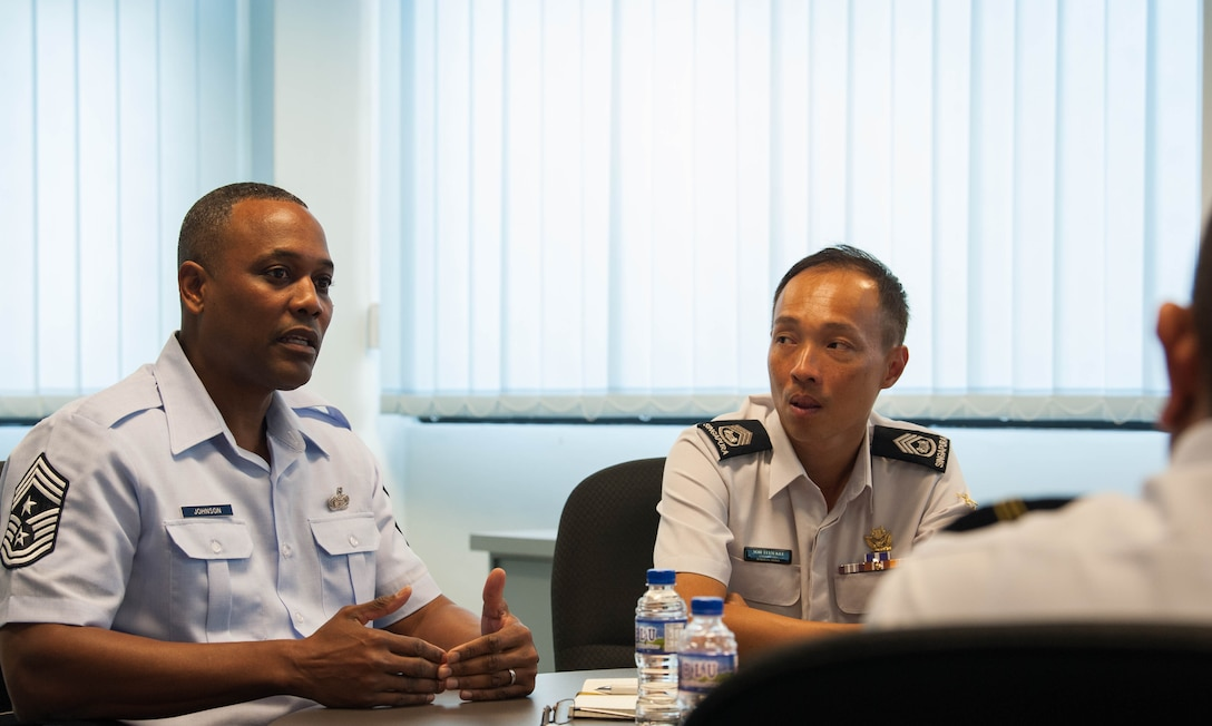 U.S. Air Force Chief Master Sgt. Anthony Johnson, Pacific Air Forces (PACAF) command chief, has a discussion with Republic of Singapore Air Force senior military experts and warrant officers during a visit to Sembawang Air Base, Singapore, March 19, 2019.