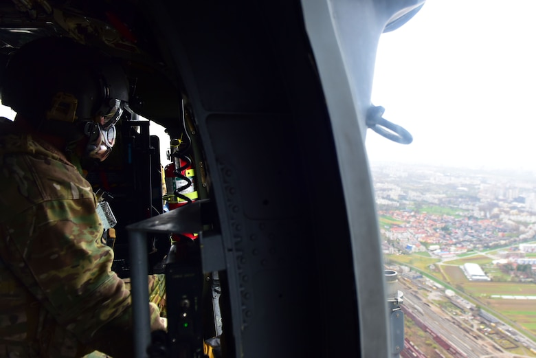 A 56th Rescue Squadron special mission aviator, stationed at Aviano Air Base, Italy, surveys a landing zone during a Non-combatant Evacuation Operation exercise near Zagreb, Croatia, March 18, 2019. Special mission aviators survey landing zones and update aircraft crew members on rescue operations. (U.S. Air Force photo by Senior Airman Kevin Sommer Giron)