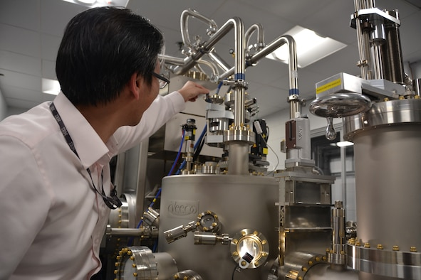 AFRL Materials Researcher Dr. Shin Mou shows off the laboratory's new Molecular Beam Epitaxy chamber, a highly-specialized piece of equipment enabling the growth of semiconducting materials for a new breed of lighter, smaller, more agile electronics. (U.S. Air Force Photo/Adrienne Kreighbaum)