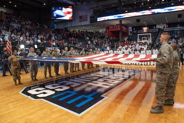 Airmen from Wright-Patterson Air Force Base, Ohio hold a large garrison-size American flag during the presentation of the colors and singing of the national anthem at the NCAA First Four Tournament March 19, 2019. (U.S. Air Force photo by Michelle Gigante)