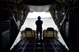 An airman looks out the back of a C-130J Super Hercules during the fly-in exercise