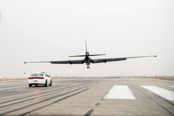 A U-2 Dragon Lady pilot drives a high-performance chase car on the runway to catch a U-2 performing a low-flight touch-and-go
