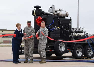 Dr. Carol Bonds, U.S. Air Force Tech. Sgt. Jayton Washington, 312th Training Squadron instructor, and Lt. Gen. Steve Kwast, commander of Air Education and Training Command, cut the ribbon for a new mobile fire pump at the Louis F. Garland Department of Defense Fire Academy on Goodfellow Air Force Base, Texas, March 20, 2019. Thanks to help from Bonds family and the city of San Angelo, Goodfellow was able to purchase four new pumps. (U.S. Air Force photo by Airman 1st Class Zachary Chapman/Released)