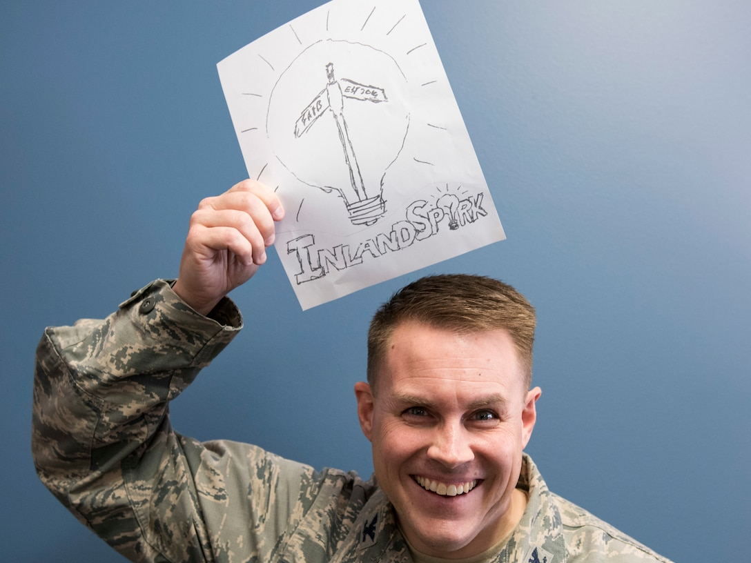 U.S. Air Force Col. J. Scot Heathman, 92nd Air Refueling Wing vice commander, holds up a logo idea for the new 'Inland Spark' thinker space being built at the Red Morgan Center at Fairchild Air Force Base, Washington, March 19, 2019. The space is an investment to empower Airmen to cultivate innovative ideas, giving them space to collaborate with others and model products. (U.S. Air Force photo by Senior Airman Ryan Lackey)