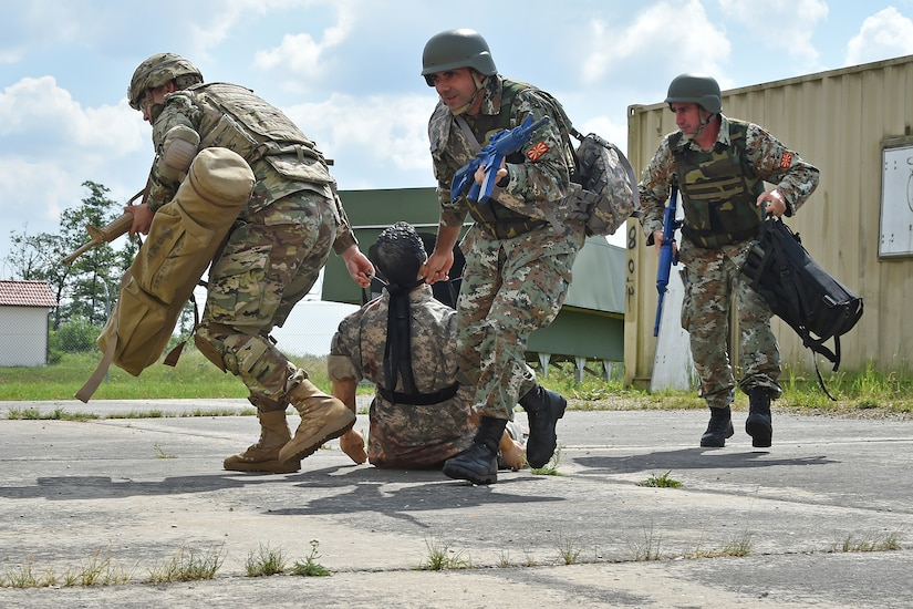 Soldiers drag a casualty training dummy away from a containerized building during training.