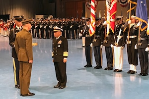 Two military men face each other as a military color guard stands behind them.