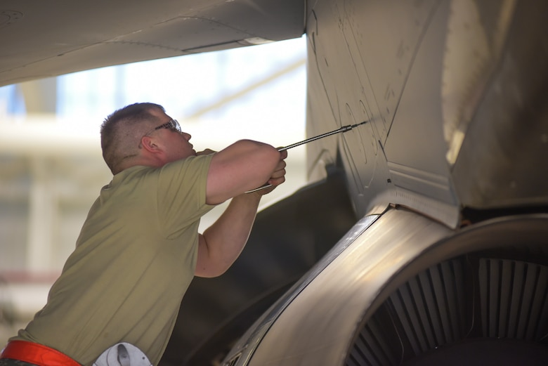 Staff Sgt. Christian Eads, 22nd Maintenance Squadron aerospace propulsion specialist, removes a panel above a KC-46 Pegasus engine March 20, 2019 at McConnell Air Force Base, Kan. The A-check team is responsible for conducting multiple operational tests to include lubricating landing gear, flight controls and engine components. (U.S. Air Force photo by Staff Sgt. Chris Thornbury)