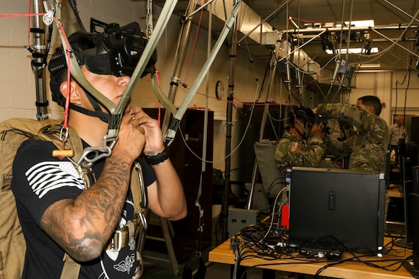 A paratrooper prepares for a virtual reality jump training on the new Parachute Simulator (PARASIM) 7 at the Joint Riggers Facility, MacDill Air Force Base, Tampa, Fla., Feb. 21, 2019. The PARASIM 7 recreates the experience of a real parachute jump from the head-mounted 3D virtual reality display to the suspension harness that detects jumper inputs. The physics-based parachute simulation technology recreates the conditions of a live jump using real-world scenes, malfunctions, wind profiles, various weather conditions and a full library of terrain types. (U.S. Army photo by Staff Sgt. Steven Colvin)