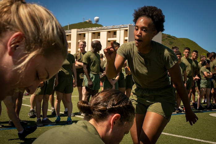 """Sgt. Erica Jackson, barracks manager with Headquarters Battalion, motivates U.S. Marines during a """"wheel barrel"""" event during a HQBN company competition at Porter Field, Mar. 15, 2019.The battalion put together this competition to build a competitive nature between Marines while also building camaraderie and cohesion within the unit. (U.S. Marine Corps photo by Cpl. Luke Kuennen)"""