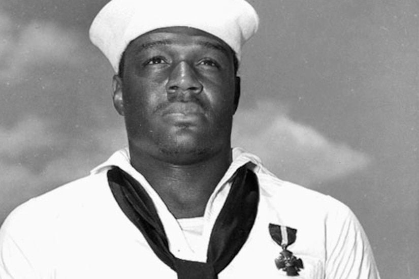 A sailor stands for a photo in a white uniform, wearing the Navy Cross on his chest.