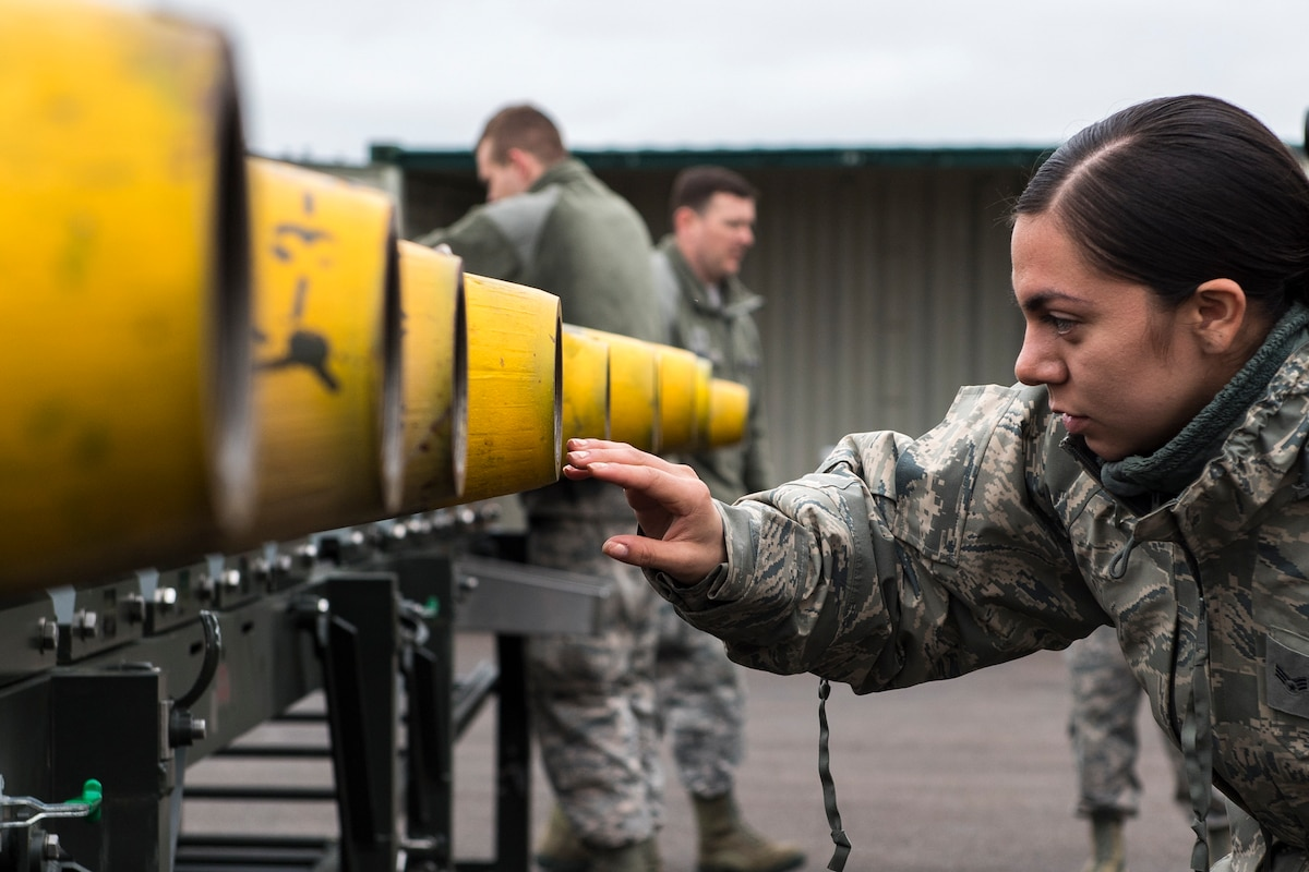 An airman touches the nose of a bomb with two airmen in the background.