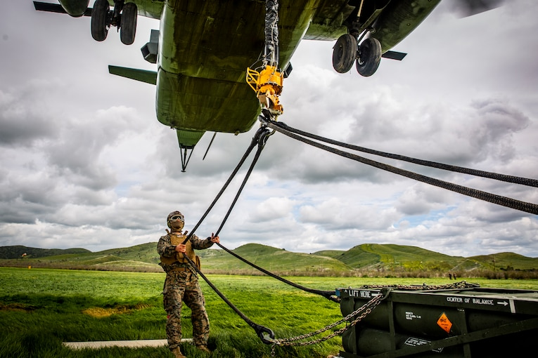 A Marine pulls two ropes hanging from a helicopter flying above.