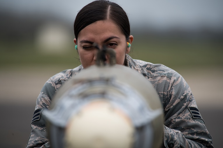 An airman looks closely at the alignment of a bomb.