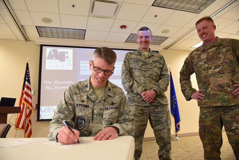 Col. Trevor Wentlandt, 460th Mission Support Group commander, fills out his 2019 Air Force Assistance Fund donation form during the Team Buckley AFAF Campaign kick-off event March 20 at the base chapel, while Capt. Kevin Feiszli (center) and Master Sgt. Jason Stonehocker (right), Team Buckley AFAF Project Officers, look on. (U.S. Air Force photo by Master Sgt. Beth Anschutz)