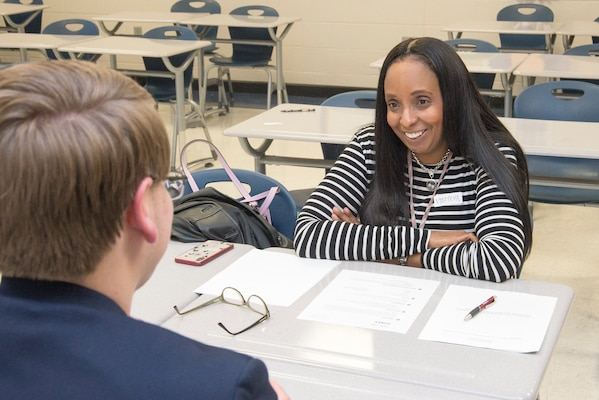 Lori Cordell-Meikle, chief of Internal Review at Huntsville Center, gives advice to Alex Montgomery, a junior at New Century Technology High School, during practice interviews as part of the school's career day March 12, 2019.