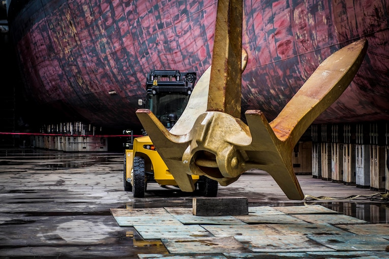 A ship's anchor sits in a dry dock with a construction vehicle parked behind it.