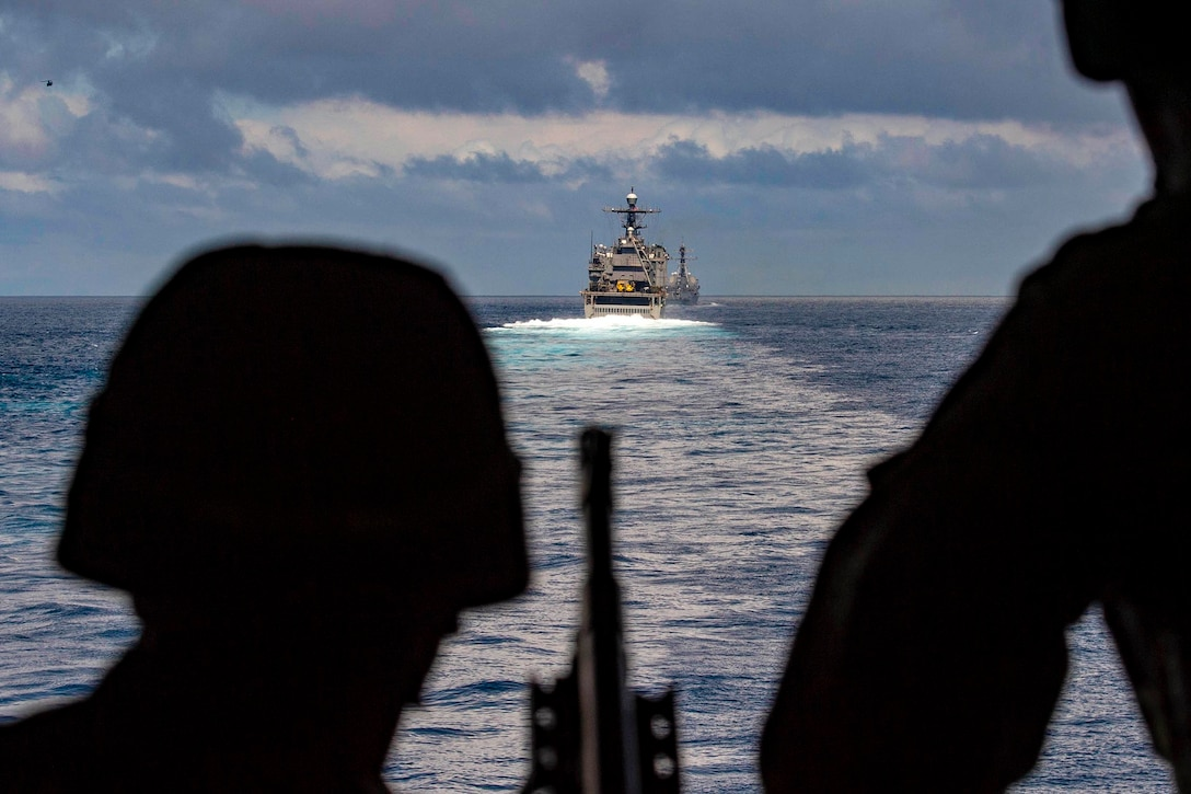 Two sailors look at two ships moving in the ocean waters.