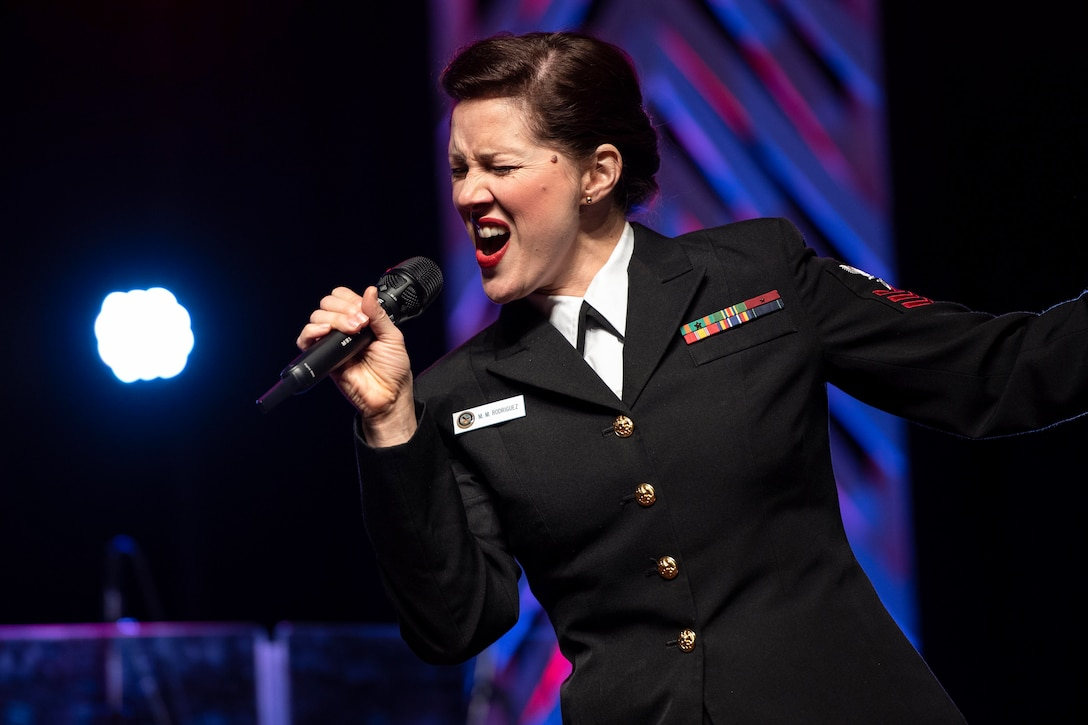 A sailor sings into a microphone.