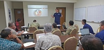 190320-N-NB178-1067 MAJURO, Republic of the Marshall Islands (March 20, 2019) U.S. Coast Guard Lt. Cmdr. Kevin Cooper speaks at a search and rescue planning meeting led by Coast Guardsmen from the U.S. Coast Guard 14th District during Pacific Partnership 2019. Pacific Partnership, now in its 14th iteration, is the largest annual multinational humanitarian assistance and disaster relief preparedness mission conducted in the Indo-Pacific. Each year, the mission team works collectively with host and partner nations to enhance regional interoperability and disaster response capabilities, increase stability and security in the region, and foster new and enduring friendships in the Indo-Pacific. (U.S. Navy photo by Mass Communication Specialist 1st Class Tyrell K. Morris)