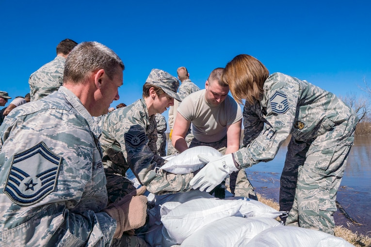 A group of airmen lay sand bags along a levee.