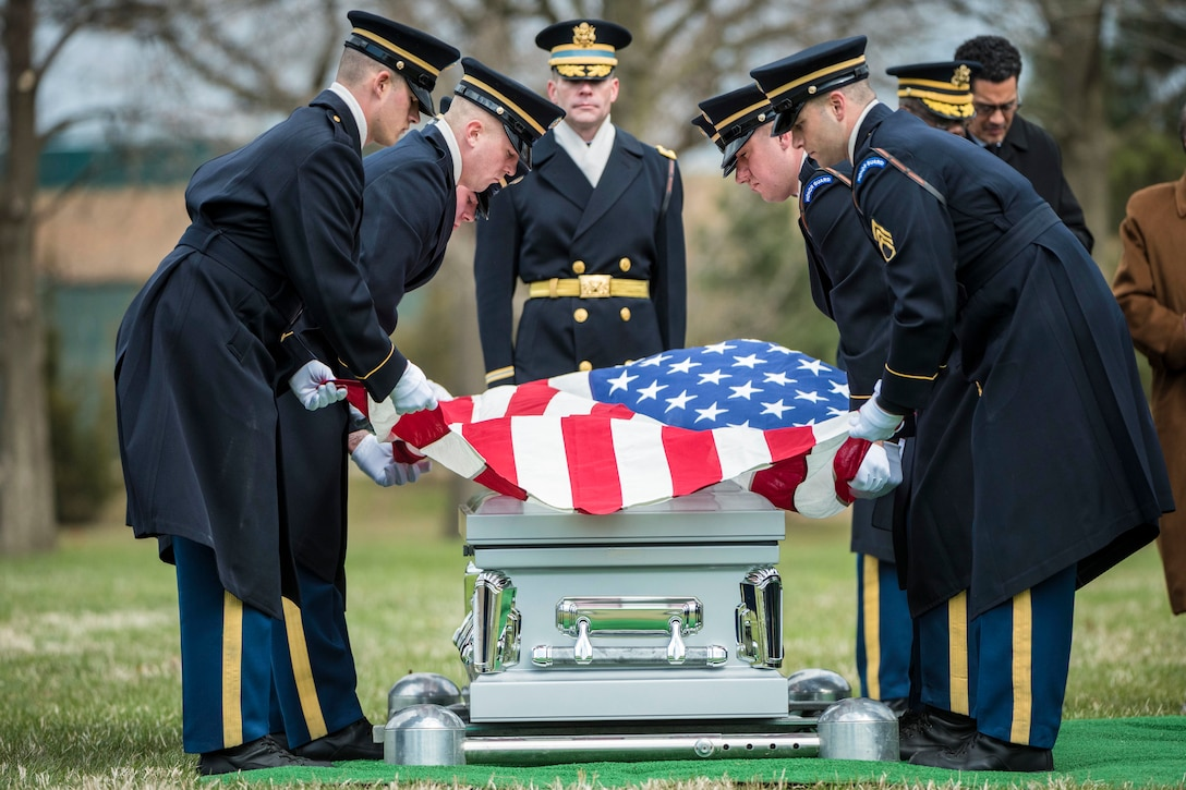 Soldiers place an American flag over a casket.