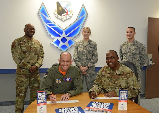 Brig. Gen. E. John Teichert, 412th Test Wing commander, and Chief Master Sgt. James Coleman, 412th TW acting command chief, pose for a photo while filling out their Air Force Assistance Fund donation forms March 22. Standing in the back, from left to right are this year's AFAF managers: Senior Master Sgt. Brian Holmes, 2nd Lt. Morgan Mavroudis and 2nd Lt. Evan Amato. (U.S. Air Force photo by Kenji Thuloweit)