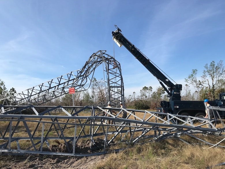 Members from the 210th Engineering Installation Squadron use a telephone main hydraulic derrick truck to remove a damaged tower at Tyndall Air Force Base, Nov. 17, 2018.