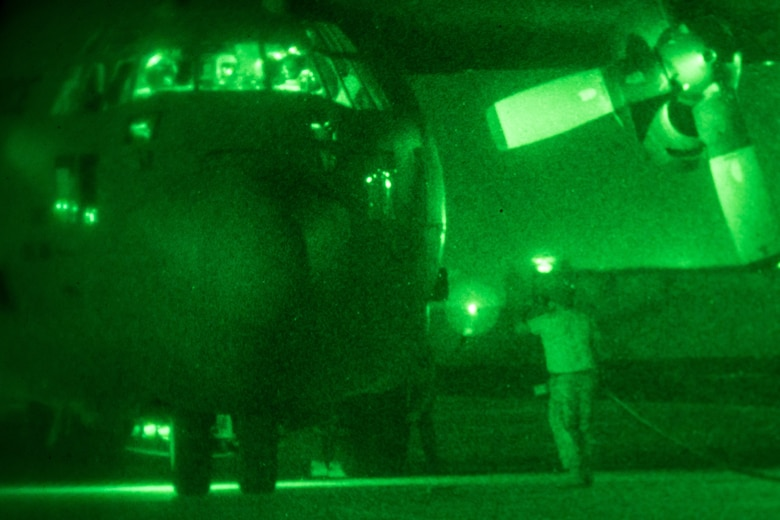 A 181st Airlift Squadron crew chief connects power to a C-130 during night vision operations July 25, 2018, at Naval Air Station Fort Worth Joint Reserve Base, Texas. The crew practiced night vision-assisted takeoff and landing procedures to demonstrate standard operating and emergency procedures to members of the wing's Chilean Air Force State Partners. (U.S. Air National Guard photo by Tech. Sgt. Lynn Means)